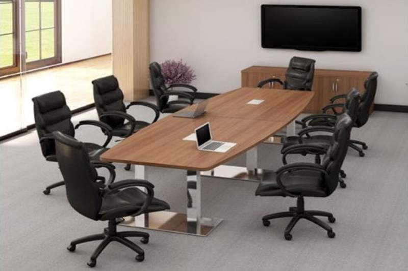 Medium sized brown conference table with a laptop on it